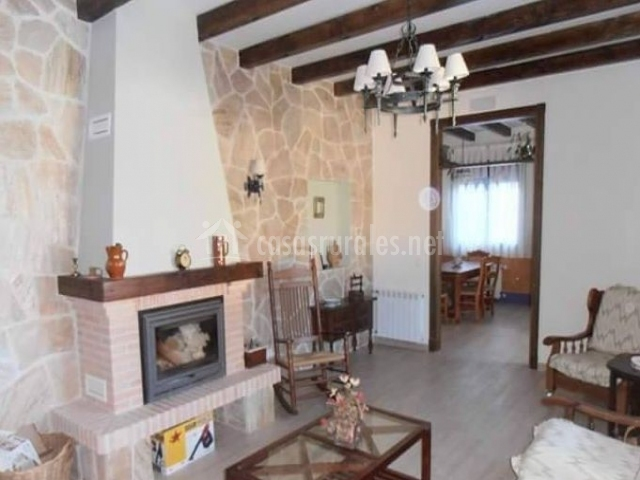 Sala de estar con chimenea y pared de piedra