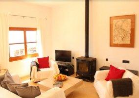 Sala de estar con chimenea junto a la cocina acristalada