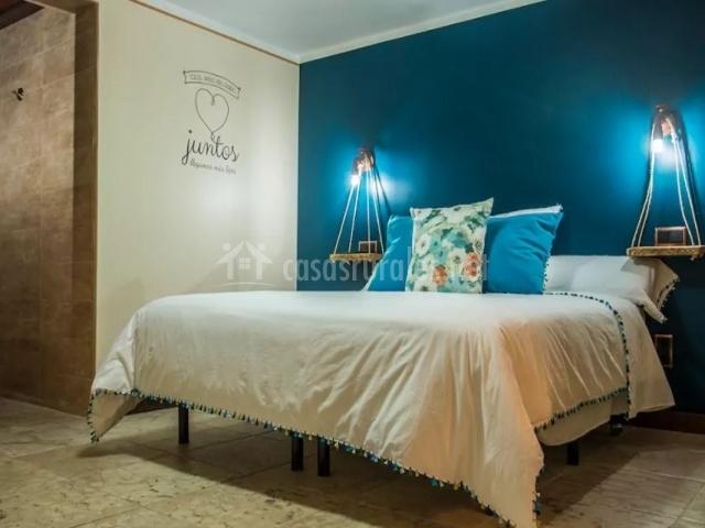 Dormitorio de matrimonio con paredes en color azul y luces