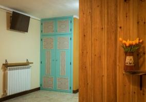 Dormitorio de matrimonio con televisor en la pared