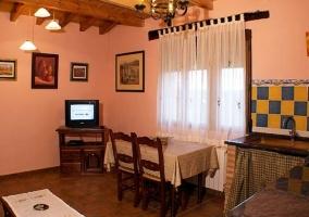 Sala de estar con televisor y mesa de madera