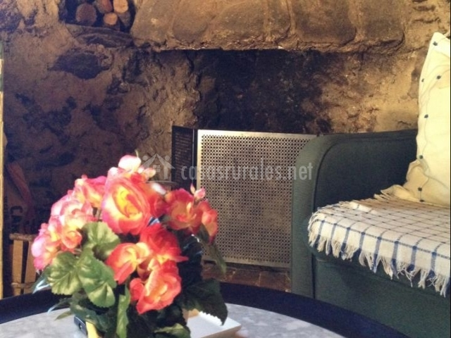 Sala de estar con la chimenea en piedra y centro de flores
