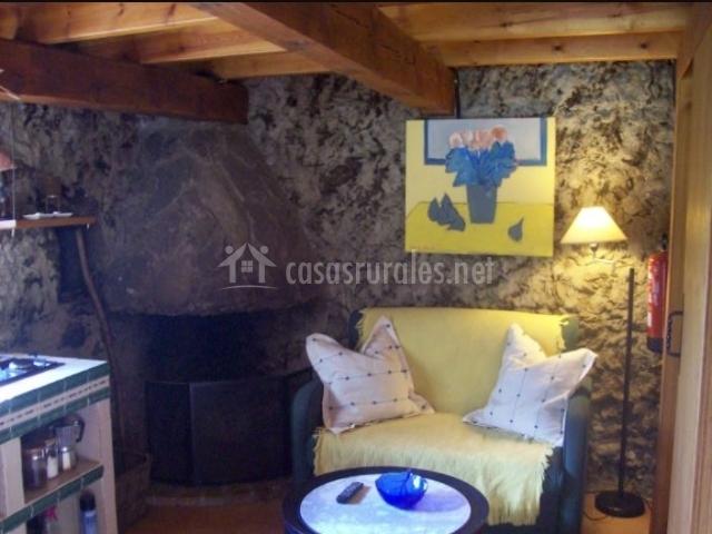 Sala de estar con la cocina junto a la chimenea de piedra
