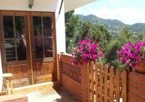 Acceso a la vivienda con puertas en madera y plantas