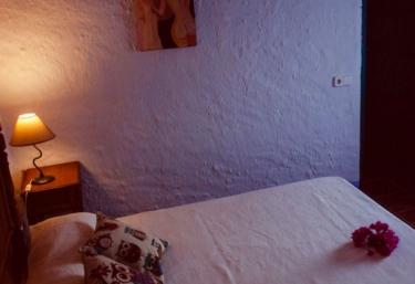 Dormitorio de matrimonio con ventana frente a la cama