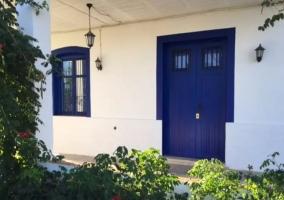 Acceso a la vivienda en azul y blanco y detalles de naturaleza