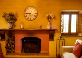 Sala de estar con la chimenea y troncos de madera