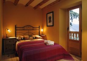 Habitación con cama de matrimonio y salida al balcón