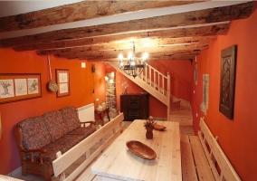 Salón-comedor con mesa y bancos de madera