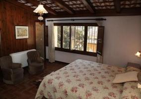 Dormitori con colchas de flores y butaca