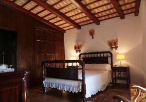 Dormitorio con cama de matrimonio y estructura en madera