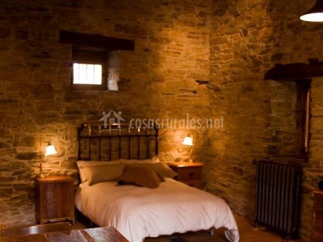 Dormitorio de piedra antigua con mesa