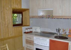 Cocina con horno, vitrocerámica, y ventana