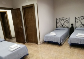 Dormitorio con varias camas y mesillas