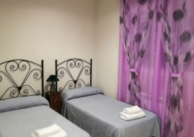 Dormitorio doble con cortinas lila