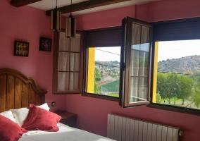 Dormitorio de matrimonio con ventanas y vistas