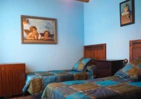 Dormitorio doble con paredes en color azul y muebles