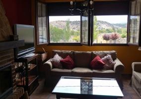 Sala de estar con mesa de madera robusta y chimenea