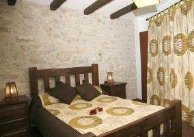 Dormitorio con vigas de madera en el techo