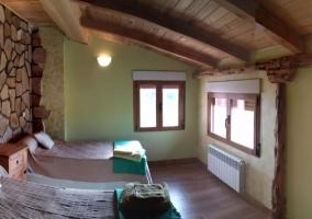Dormitorio de matrimonio con suelos de madera y ventanas