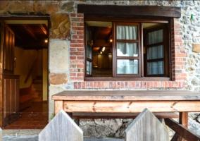 Acceso a la casa con fachada de piedra y valla de madera