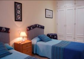 Dormitorio doble con colchas en color azul y armarios