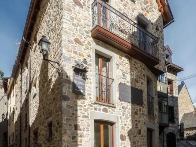 Acceso a la casa con fachada en piedra y en el casco urbano