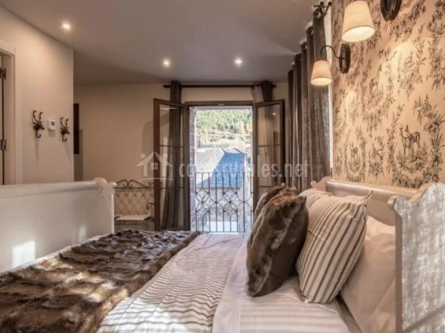 Dormitorio de matrimonio con papel pintado y mantas