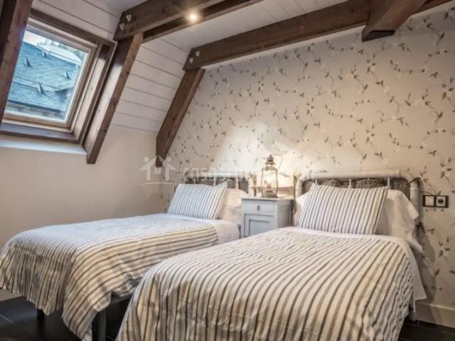 Dormitorio doble abuhardillado con papel pintado