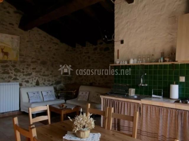 Cocina con mesa de madera y la sala de estar al fondo