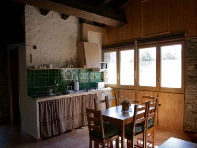 Cocina con mesa de madera y menaje