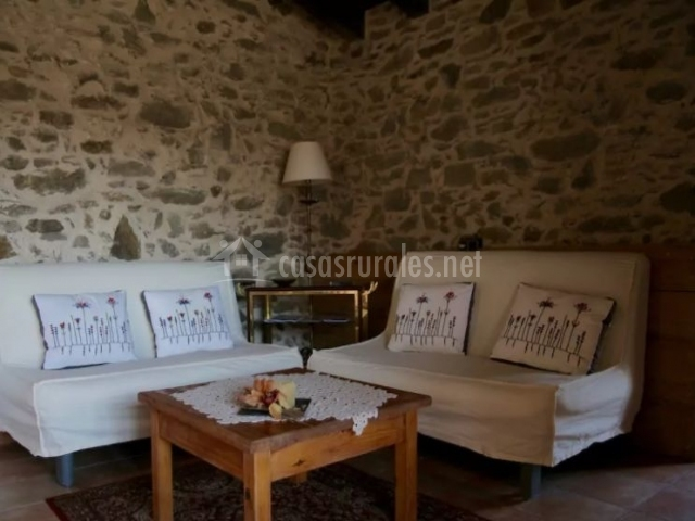 Sala de estar con paredes en piedra y sillones