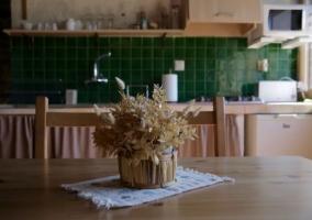 Cocina de la casa con mesa de madera y centro floral