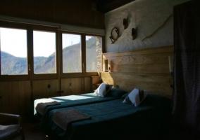 Dormitorio doble con cabecero en madera y ventanas