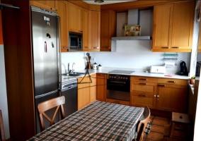 Cocina comedor con mesa alargada y mantel