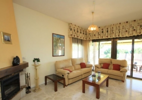 Sala de estar con la chimenea en esquina y sillones