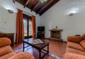 Sala de estar con sillones en naranja junto a la cocina