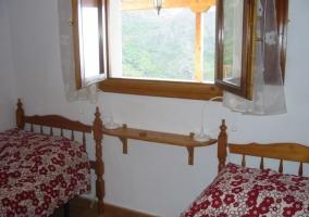 Dormitorio doble con ventana entre las camas