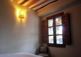 Dormitorio de matrimonio con colcha y ventanas