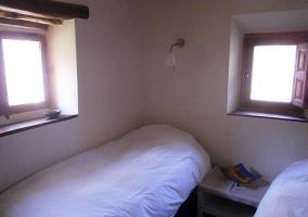 Dormitorio de matrimonio con ventana y silla en una esquina