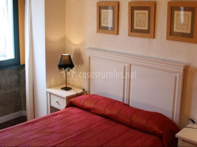 Dormitorio de matrimonio naranja con cuadros