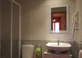 Baño en tonos grises con espejo