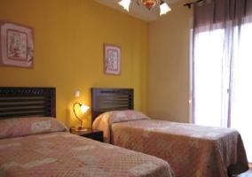 Dormitorio con dos camas twin y cortinas en morado