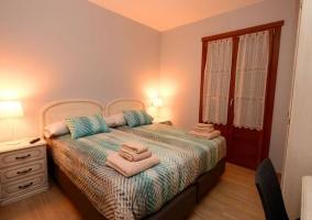 Dormitorio doble con suelo de madera y toallas