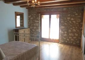 Dormitorio con cama de matrimonio con paredes de piedra