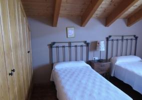 Dormitorio doble con techo de madera y mesilla