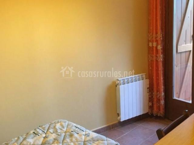 Dormitorio con cama individual y salida a la terraza