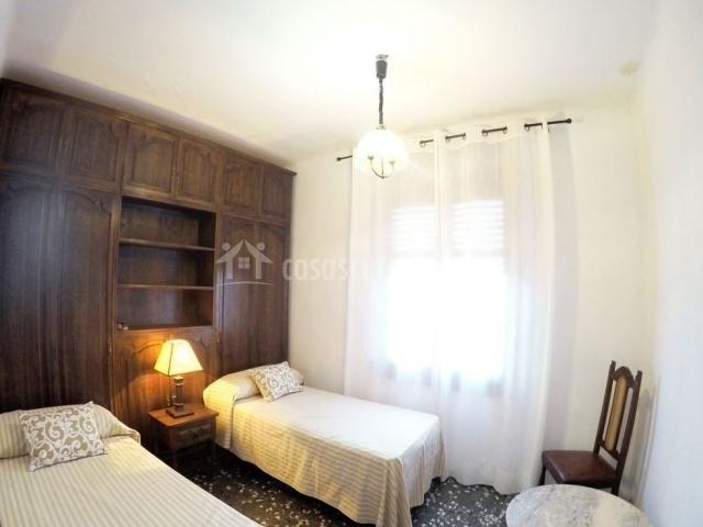 Dormitorio doble con pared de madera y mesilla