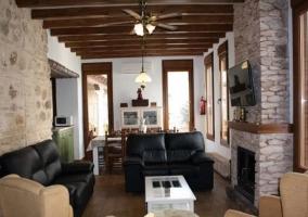 Sala de estar con sillones negros y la chimenea