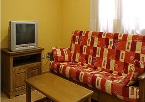 Sala de estar con sillones y televisor junto a la mesa